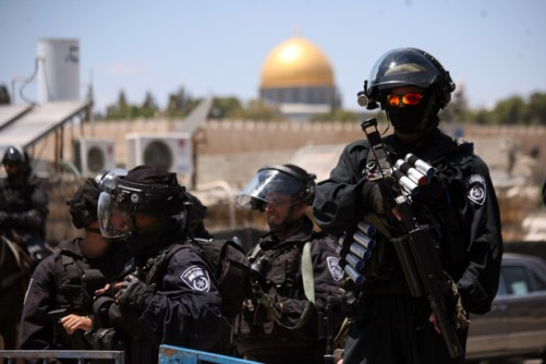 Israeli armed policemen stand guard behind Palestinian Muslims performing the traditional Friday prayers near the Old City in East Jerusalem